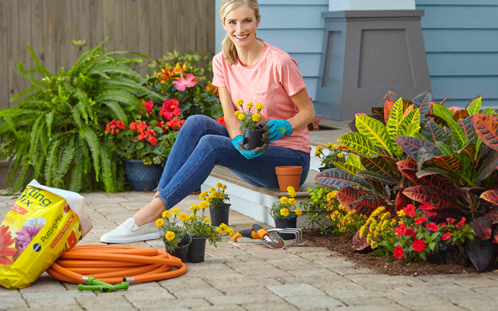 A woman sits in her garden surrounded by plants and gardening tools.