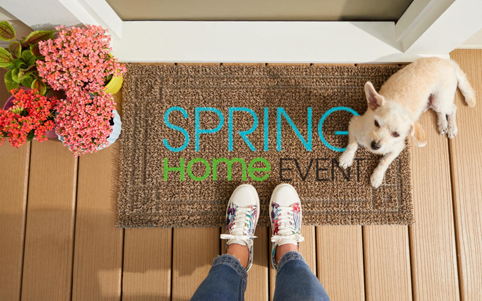 spring home event. a friendly dog sits on a welcome mat
