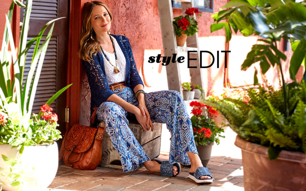 Style Edit. Woman in boho clothes sits on a colorful patio.