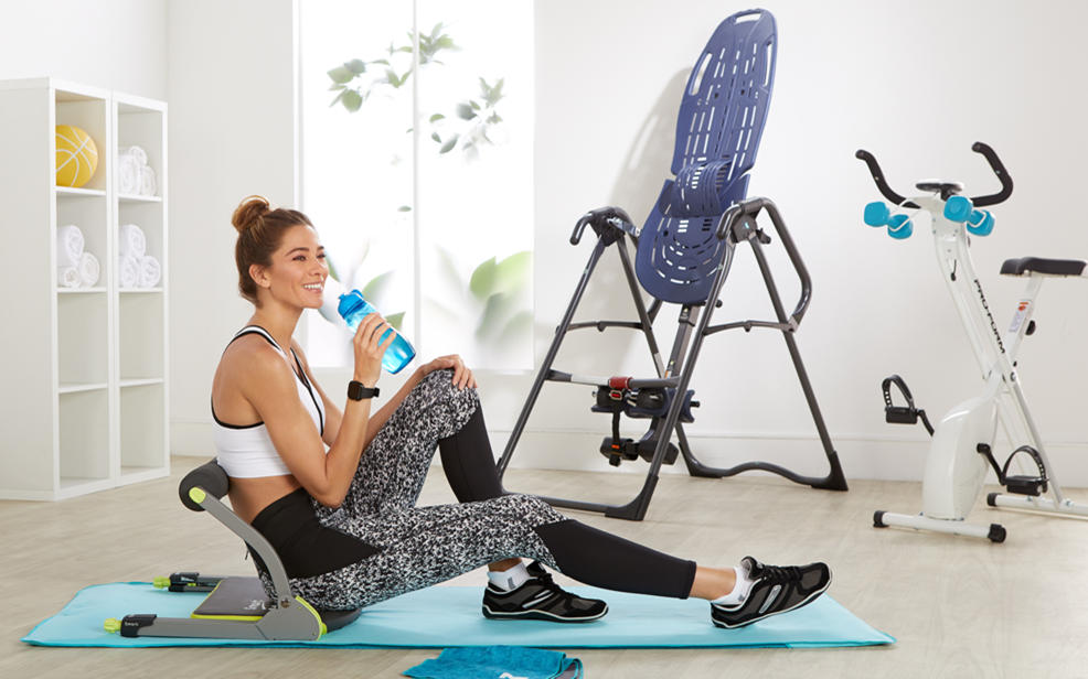 A woman drinks water amidst exercise equipment
