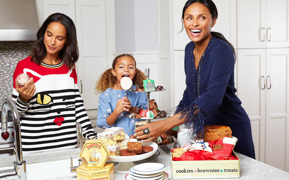 two woman and a little girl enjoying sweet treats in the kitchen