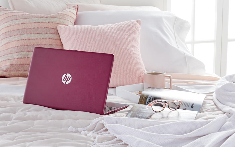 a laptop on a bed next to some coffee
